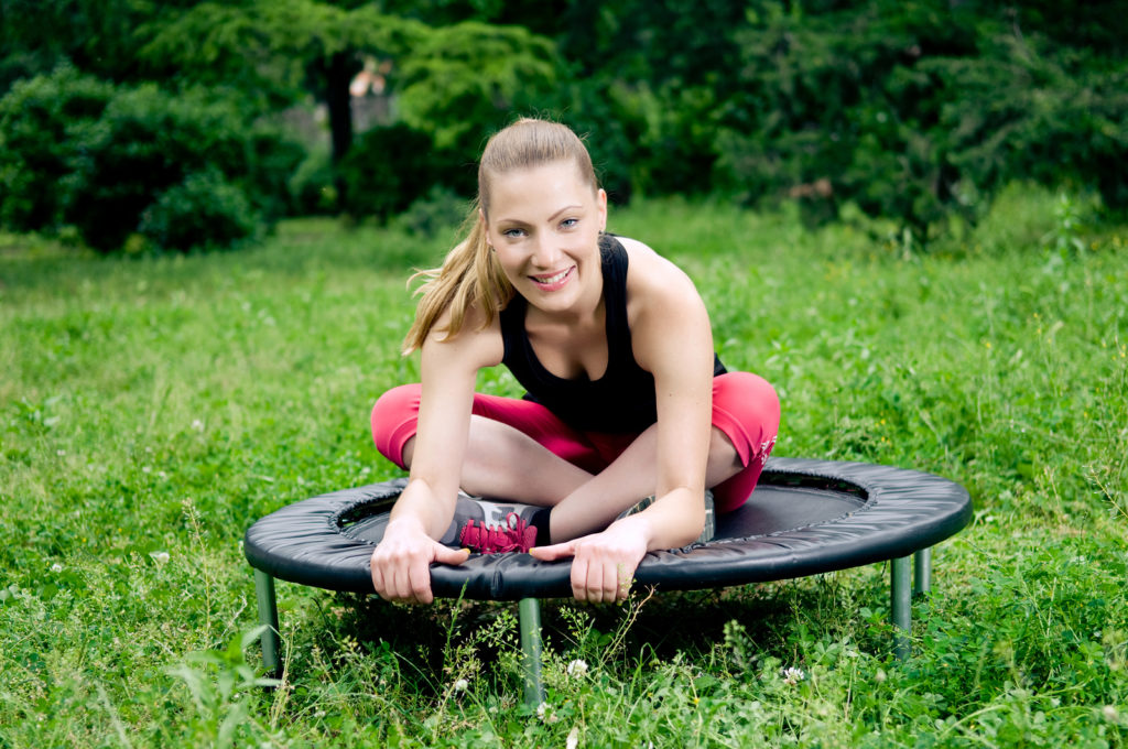 Relaxed woman in nature sitting on mini trampoline
