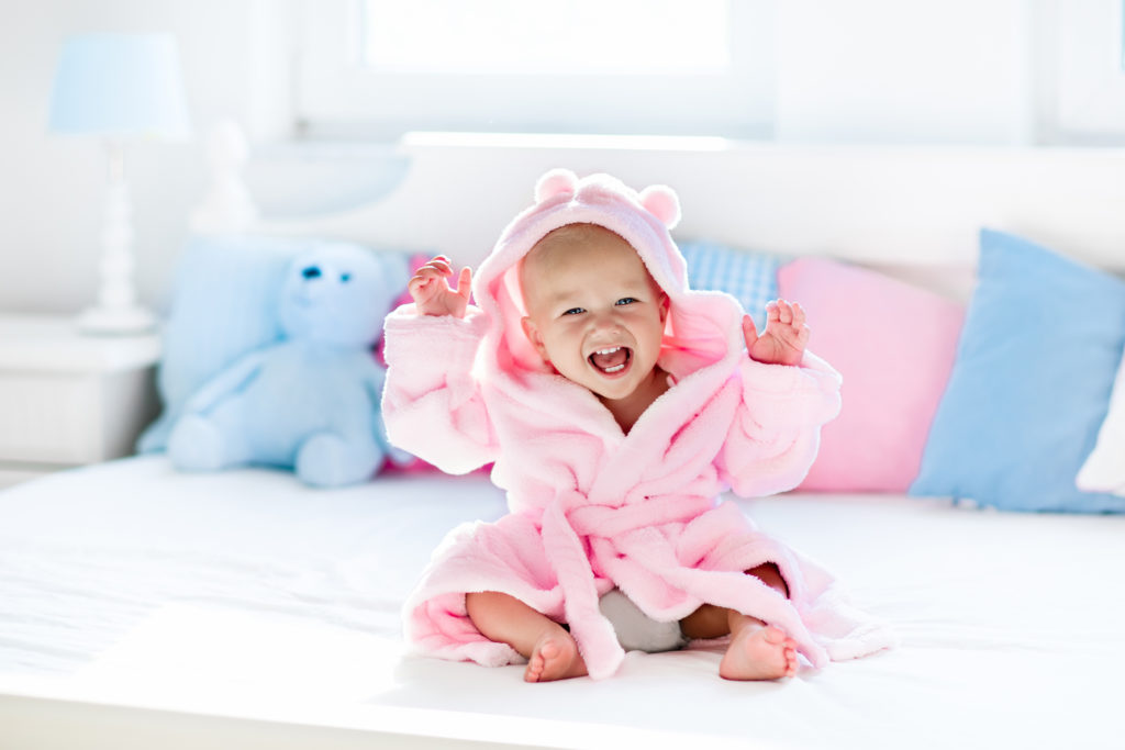 Cute happy laughing baby in soft bathrobe after bath playing on white bed with blue and pink pillows in sunny kids room. Child in clean and dry towel. Wash infant hygiene health and skin care.