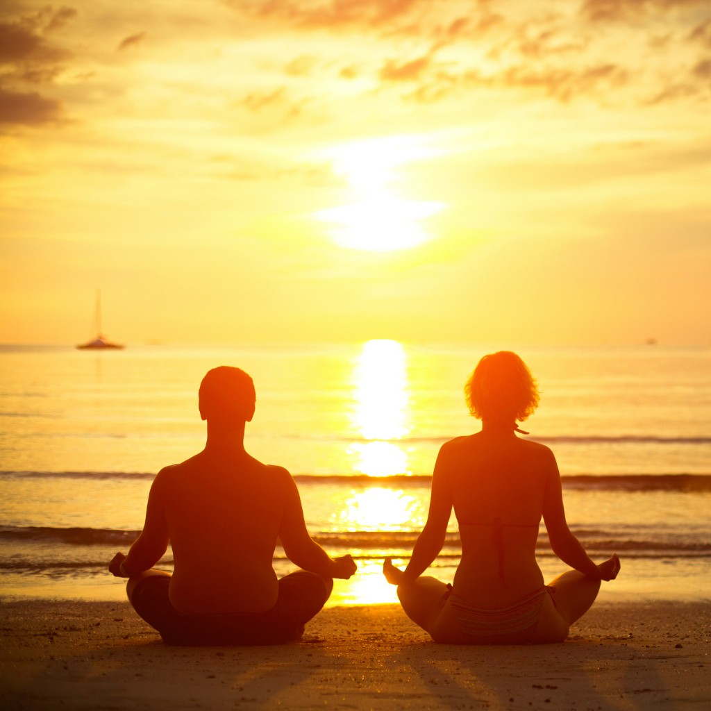 Young couple in a lotus position meditating on the beach at suns